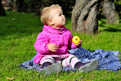 Small girl sits on green glade with apple Royalty Free Stock Photo