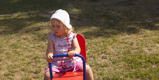 Small girl sits on the seesaw Stock Photography