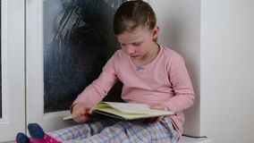 Small girl sits on windowsill behind the frozen window. Cute little girl sits on window ledge and reads the diary. stock video