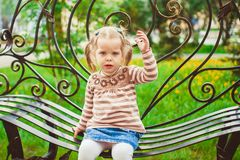 Girl sitting on the bench Stock Photography