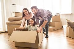 Small girl is sitting in box and pretending she is in a car. Her parent are moving the box straight forward. Everybody. Is having a lot of fun Stock Images