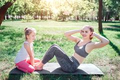 Small girl is sitting on carimate and holding feet of her mom while woman is doing some abs excercises. She is kepping. Small girl is sitting on carimate and Royalty Free Stock Image