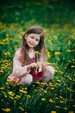 Small girl sitting in flower field and feel happy. Pretty small girl with long brown hair sitting in field of flowers Stock Image