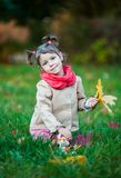 Small girl sitting on the grass in the park. Small girl outdoor in the park with yellow leaves Stock Images