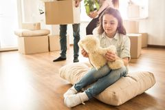 Small girl is sitting on the pillow on the floor and looking to her teddy bear toy. She has some rest while her parents. Are holding boxes with things and Stock Photography