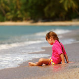 Small girl sitting on sand Stock Images