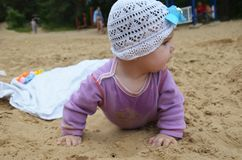 Small girl sitting on sand at beach Royalty Free Stock Images