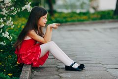 Small girl sitting under the cherry tree Royalty Free Stock Photography