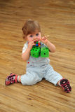 Small girl sitting on wooden floor and play with toys Royalty Free Stock Photography