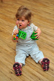 Small girl sitting on wooden floor and play with toys Stock Image