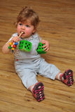 Small girl sitting on wooden floor and play with toys Stock Photos