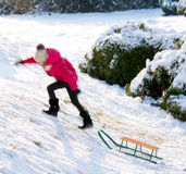 Small girl sledding at winter time Stock Photo