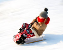 Small girl sledding at winter time Royalty Free Stock Image