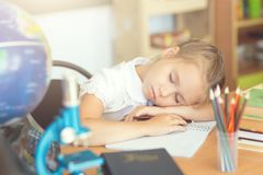 Small girl sleeping on a desk in a classroom.  Royalty Free Stock Image