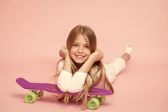 Small girl smile with skate board on pink background. Child skater smiling with longboard. Skateboard kid lie on floor. Childhood lifestyle and active games stock photos