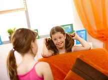 Small girl smiling at friend in living room Royalty Free Stock Photo