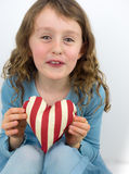 Small girl smiling and holding a valentine heart Royalty Free Stock Photos