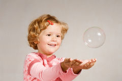 Small girl with soap bubble. Small beautiful girl looking at a soap bubble Stock Photos