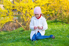 Small girl in spring park. Happy small girl gather gowan flowers near blossoming yellow Forsythia bush Stock Photography