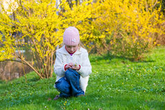 Small girl in spring park. Happy small girl gather gowan flowers near blossoming yellow Forsythia bush Stock Photos