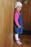 Small girl  standing. By the wall Stock Image