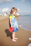 Small girl standing on beach Stock Images
