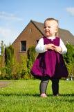 Small girl standing near the house Stock Photos
