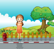 A small girl standing near the wooden fence Royalty Free Stock Photos