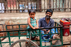 Small girl standing on the trunk of her father rickshaw pedicab Royalty Free Stock Images