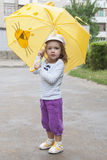 Small girl standing with the yellow umbrella Stock Photography