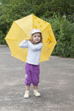 Small girl standing with the yellow umbrella Royalty Free Stock Images