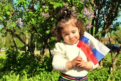 Small girl stands with flag of Russia in front of lilac Bush on sunny day. Russian translation on flag: Russia Stock Images