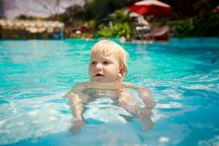 small girl stands on fours in shallow transparent pool water Royalty Free Stock Images