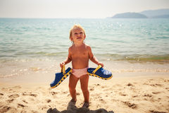 small girl stands on sand holds father's slippers by azure sea Royalty Free Stock Image