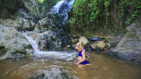 Small Girl Starts to Swim in Stream Water by Waterfall stock footage