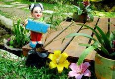 Small girl statue in the garden Stock Photos