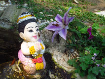 Small girl statue in the garden. Small girl colorful statue in the flower garden royalty free stock photos