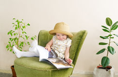 Small girl in straw hat reads book at home.  Royalty Free Stock Photos