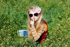 Small girl with sunglasses with fingers at lips Stock Image