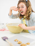 Small girl tasting cookie dough Stock Images