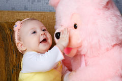 Small girl touch toy bear Royalty Free Stock Photo
