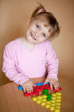 Small girl with toy mosaic. Fun baby girl put hands on mosaic's parts and smile Stock Photos
