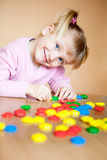 Small girl with toy mosaic. Fun baby girl play with mosaic's parts and smile Stock Photos