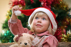 Small girl with toy near christmas tree Stock Image