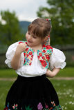 Small girl in traditional dress on the meadow Stock Photos