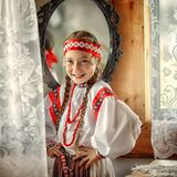 A small girl in a traditional Russian costume on the background of a mirror