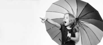 Small girl with umbrella in rainy weather. Surprised little girl with umbrella, copy space. Feeling protected at autumn stock images