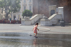 Small girl using  water curtain in sunny hot day, Krakow, Poland Royalty Free Stock Photos