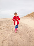 Small girl walking on the beach in winter Stock Photos