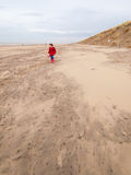 Small girl walking on the beach in winter Stock Images
